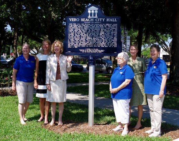 Six women standing by City Hall dedication sign